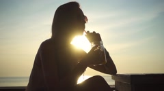 Girl Drinks Beverage Sitting in a Chill Cafe on the Sunset. Slow Motion Stock Footage