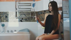 Attractive girl sitting on toilet in bathroom. Take selfie on blue monopod Stock Footage