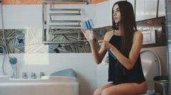 Attractive girl sitting on toilet in bathroom with blue monopod for selfie Stock Footage