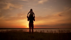 Silhouettes of dad and son playing, rejoicing in field at sunrise. Slow motion Stock Footage