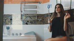 Attractive girl sit on toilet posing for selfie on blue monopod. Touch hair Stock Footage