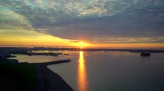 Aerial view on sunrise over sea shore, calm water, ports and city Stock Footage