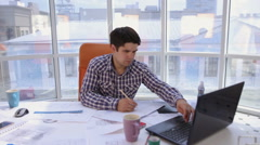 A confident and attractive businessman working with drawings, blueprints in a Arkistovideo
