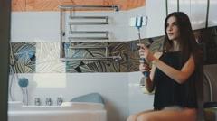 Brunette girl sit on toilet posing for selfie on monopod. Touch hair. Bathroom Stock Footage