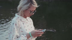 Young beautiful woman using her smartphone in the city park near the lake Stock Footage
