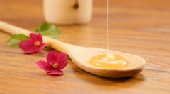 Pouring honey on a spoon. Composition with flowers (No 2) Stock Footage