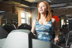 Young strong girl running on treadmill in gym Stock Photos
