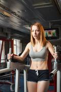 Young strong girl do leg lift for abs in gym Stock Photos