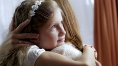Close-up of cute little girl embracing her loving mother at home Stock Footage