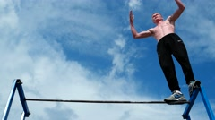 The athlete performs exercises on the cross-bar, horizontal bar Stock Footage