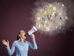 Young woman screaming into a megaphone Stock Photos
