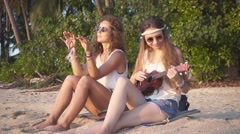 Hippie Girls Having Rest Sitting on a Sand on the Beach at Sunset. Slow Motion Stock Footage