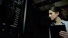 A young female IT engineer is working in a data center Stock Footage