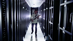 A young IT engineer and wannabe rock star is working in a data center Stock Footage