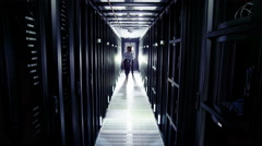 A man and a woman of mixed ethnicity are working in a data centre Stock Footage