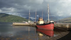 'Vital Spark' trawler in the scenic loch harbour Stock Footage