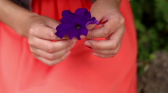 Woman hands holding purple flower red bloom hidden in arms. Static closeup shot Stock Footage