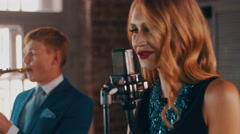Vocalist with red lips perform on stage at concert microphone with saxophonist Stock Footage