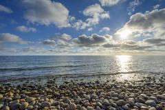 Sky with Clouds and Sun over pebble Beach, Summer, Sealands Odde, Odsherred, Stock Photos