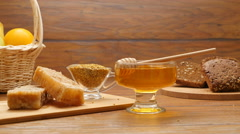 Composition of honey, honeycomb, fruits, brown tommy and bee bread (RL Pan) Stock Footage