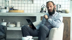 Happy businessman with tablet telling good news to camera sitting on armchair in Stock Footage
