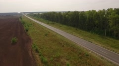 Drone flying over asphalt road with cars, near black plowed field and forest in Stock Footage
