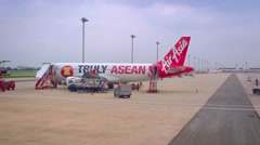Ground support vehicles approach Air Asia passenger plane at Don Mueang Airpo Stock Footage