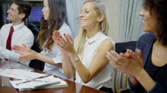 Young attractive business group are seated around a conference table for a Stock Footage