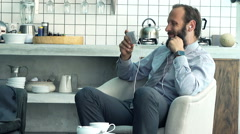 Businessman watching movie on smartphone and drinking coffee on armchair  Stock Footage