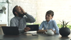 Unhappy businesspeople with tablet sitting by table in open kitchen at home Stock Footage