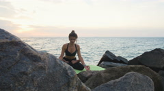 Young attractive female doing yoga exercises on the rocks near the water Stock Footage