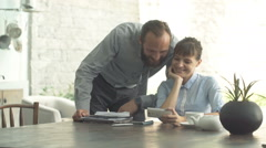 Happy businesspeople watching movie on smartphone by table in open kitchen at ho Stock Footage