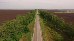 Drone flying over asphalt road between two plowed fields in countryside, cars Stock Footage