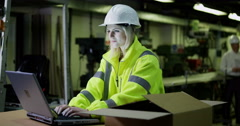 4K Female worker in industrial environment working on laptop Stock Footage