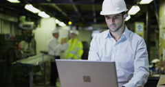 4K Business manager in industrial environment working on laptop Stock Footage