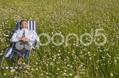 Mann relaxt auf einer Blumenwiese Stock Photos