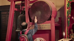 Buddhist worshiper strikes a drum and a bell after donating money Stock Footage