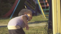 Baby girl playing hide and seek with her mother at the playground, slow motion Stock Footage