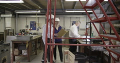 4K Staff members working within a busy warehouse or factory Stock Footage
