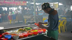 Local man prepares food at a street vendor's stand during a heavy rain Stock Footage
