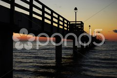 Pier going out into the Baltic Sea at dusk Stock Photos
