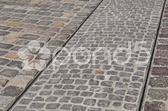 Tracks of a tram on a cobblestone pavement Stock Photos