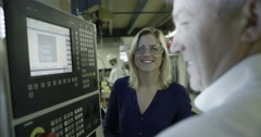 4K Business manager in factory showing woman how to operate machine Stock Footage
