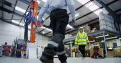 4K Foreman & workers getting on with the job in large factory warehouse Stock Footage