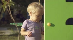 Little girl playing on Playground, hiding behind the gaming facilities Stock Footage