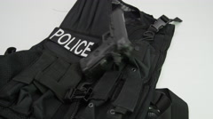 Gun landing on police tactical vest Stock Footage