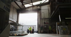 4K Workers moving goods around through the open doorway of a warehouse Stock Footage