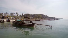 Longtail boat approaching a crowded beach in Phuket, Thailand Stock Footage