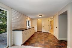 Empty room with a washbasin cabinet and brown tile floor. Northwest, USA Stock Photos