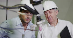 4K Mature male factory manager explains to younger man how the machinery works Stock Footage